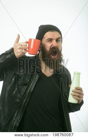 Food and drink. Hipster in hat with yoghurt and cup. Dieting and health. Ecology product and glass. Man with long beard hold milk bottle.