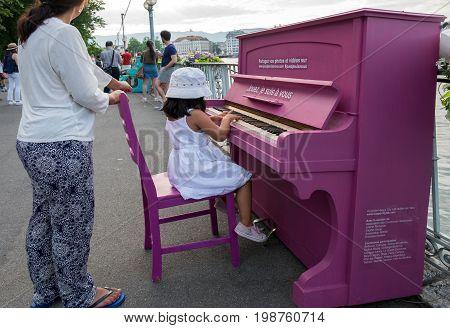Undefined Little Girl Play On Piano On Embankment On Geneva Lake