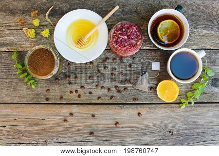 Tea, coffee in cups, chicory, lemon, mint, jam made of rose petals, dried lime, honey on the old wooden background. Toned image. Top view.
