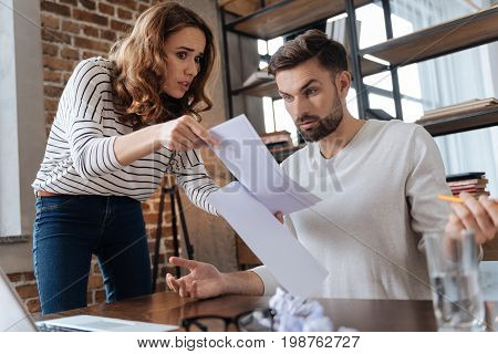 Look at these. Sad angry young woman holding documents and showing them to her boyfriend while having questions to him