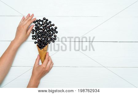 Top View Of Waffle Cone With Sweet Fresh Blackcurrants In Girl's Hand, Free Space. Fresh Black Curra