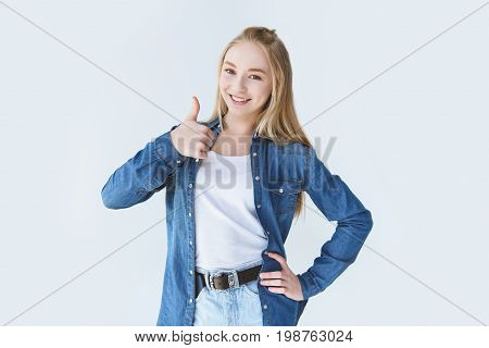 Smiling Teenage Akimbo Girl Showing Thumb Up And Looking At Camera Isolated On White