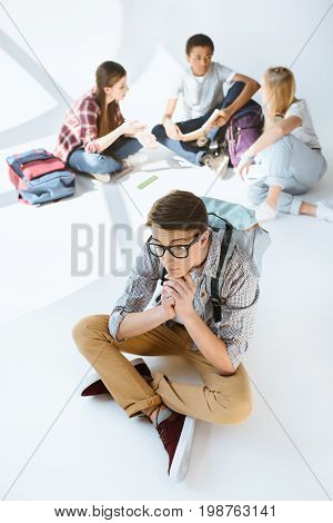 Teenage Boy Sitting Alone While Multicultural Group Of Students Resting After Classes Together Isola