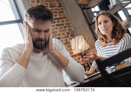 Having an argument. Unhappy pleasant young woman shouting at her boyfriend and feeling angry while being mad at him