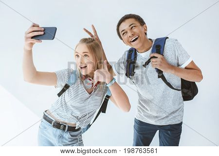 Multicultural Happy Teenagers Taking Selfie Together On Smartphone Isolated On White