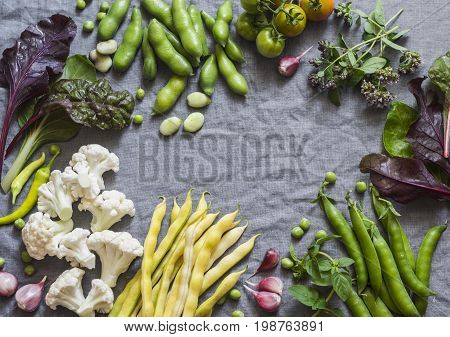Food background. Fresh garden vegetables on grey background top view. Cauliflower beans peas chard fava beans - organic veggies. Flat lay