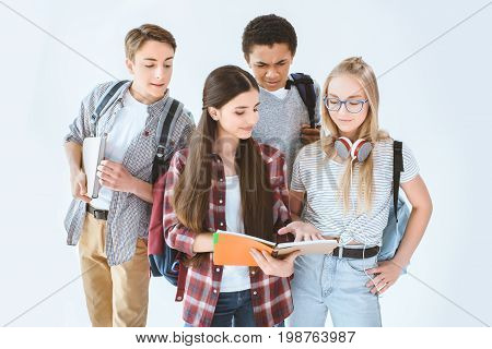 Teenage Girls Discussing Homework While Multicultural Boys Looking Out From Behind Isolated On White