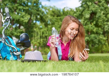 Beautiful blond haired woman smiling happily using her smart phone holding a bottle of water while lying on the grass at the park after cycling lifestyle activity fitness health technology communication.