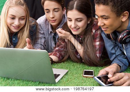 Portrait Of Multicultural Smiling Teenagers Using Laptop Together While Resting On Green Grass