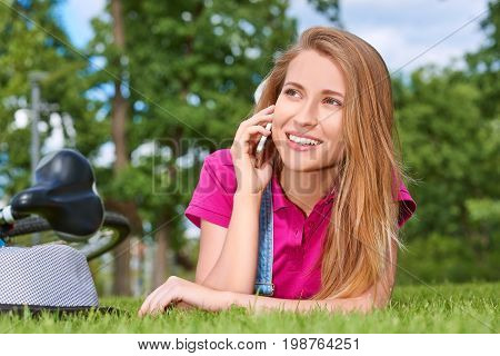 Young beautiful woman smiling talking on her smart phone lying on the grass at the local park communication chatting carrier mobility lifestyle holidays relaxation concept.