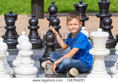 Chess game with giant chess piece. Boy siting and playing strategic outdoor game on black and white chess board