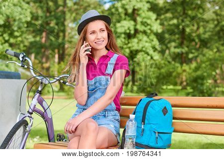 Shot of a young beautiful woman sitting on the bench at the park relaxing after cycling talking on her mobile phone copyspace technology gadget leisure travel tourism communication.