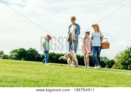 Happy Young Family With Picnic Basket Walking With Dog On Green Lawn