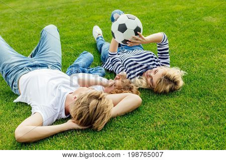 Happy Young Family With One Child Playing With Soccer Ball While Lying On Grass