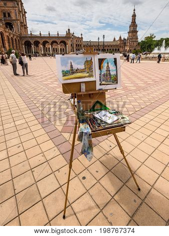Seville Spain - May 20 2014: Artists easel and artwork set up on the Spain Square (Plaza de Espana) Seville Spain.