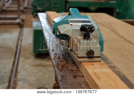 Front view of electric planer on the wooden plank in carpentry workshop