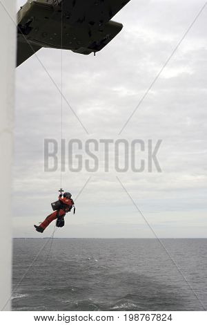 Kattegat Sea - July 22 2017: Royal Danish Air Fore rescue helicopter M-514 conducting a rescue exercise on ferry Margrete in Kattegat Sea on its way to Laesoe island in Denmark.