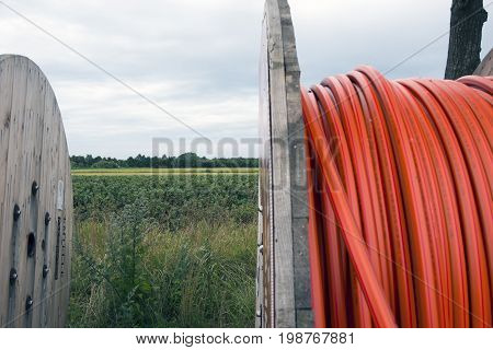 Laesoe Denmark - July 27 2017: Fiber optic cable for fast internet ready to dig down on Laesoe island in Kattegat Sea Denmark.Black currant field in the background.