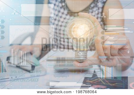 Business women hand holding light bulb with technology graph. concept of new idea with innovation and creativity.