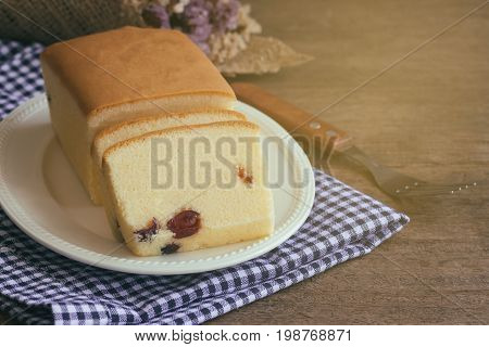 Slices of butter cake on white plate put on plaid napkin. Homemade butter cake with dried cranberries so delicious soft and moist. Tasty pound cake or butter cake ready to served on rustic wood table. Homemade bakery concept for background.
