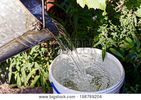 Transfusion of water from an iron bucket into a plastic bucket