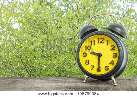 Closeup black and yellow alarm clock for decorate show half past nine o'clock or 9:30 a.m. on old brown wood desk on green leaves in the park textured background