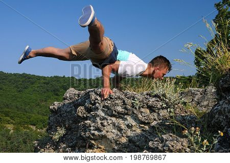 Young Caucasian man is hand balancing on the rock in the Balkan mountains