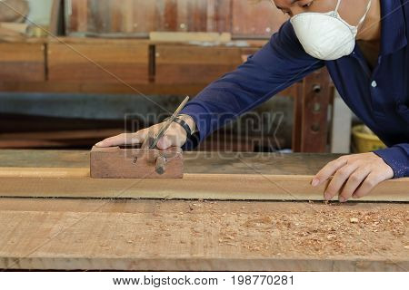 Carpenter working with a hand planer on a plank of wood in carpentry workshop. He is wearing safety equipment .