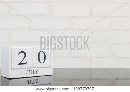 Closeup white wooden calendar with black 20 july word on black glass table and white brick wall textured background with copy space in selective focus at the calendar