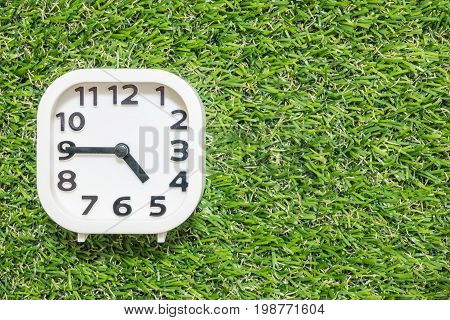 Closeup white clock for decorate show a quarter to five o'clock or 4:45 p.m. on green artificial grass floor textured background with copy space