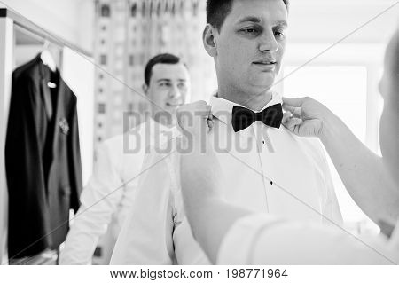 Helpful Groomsmen Or Bestmen Helping Groom To Get Ready For His Wedding. Black And White Photo.