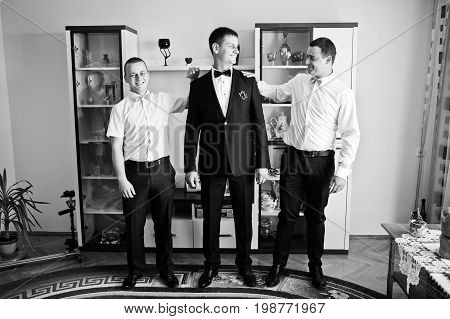 Handsome Groom Posing With His Groomsmen In The Room On The Wedding Day. Black And White Photo.