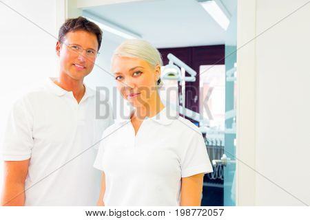 dentist and his assistant standing in front of doctor's office