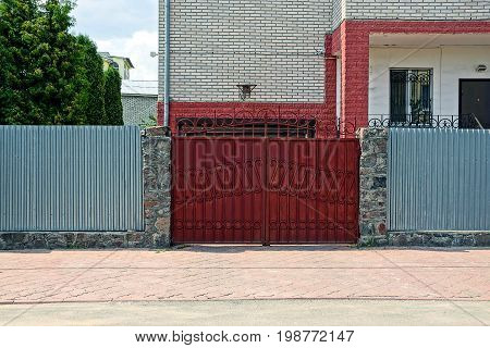 Red closed door and an iron fence in front of the facade of a private house