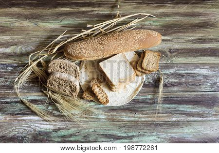 A variety of baked goods and ears of wheat on a wooden table close-up