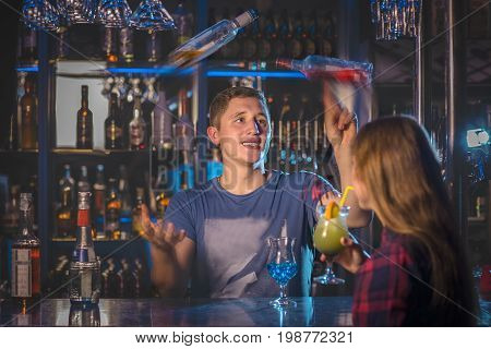 A young handsome barman shows the girl the masterly art of juggling bottles with alcohol. Background of bar supplies and bottles. Dark background.