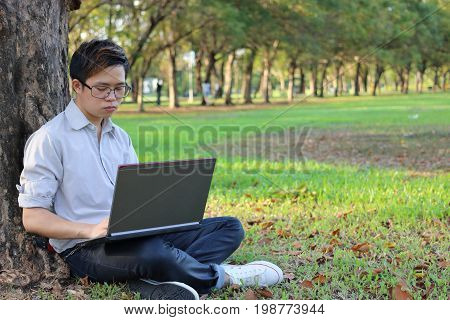 Portrait of a serious young businessman working on his laptop computer in city park with copy space background.