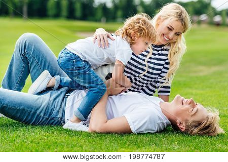 Happy Young Parents With Cute Little Son Holding Soccer Ball And Having Fun At Park