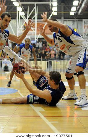 DOMBOVAR, HUNGARY - NOVEMBER 7: Szoke (8), Vojvoda (in blue) and Deak (R) in action at Hungarian National Championship basketball game, Dombovar vs Kaposvar, on November 7, 2009 in Dombovar, Hungary.