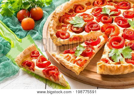 Delicious homemade pie with cheese cottage cheese pepper rolled up in roll in form of flower. Large cake on wooden round plate slice on scapula cherry tomatoes parsley on green gauze napkin