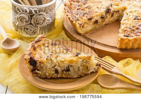 Delicious homemade quiche with cabbage and dried prunes. Vegetarian pie. Large pie and slice on wooden plates yellow gauze napkin white wooden table. Rustic style. Selective focus