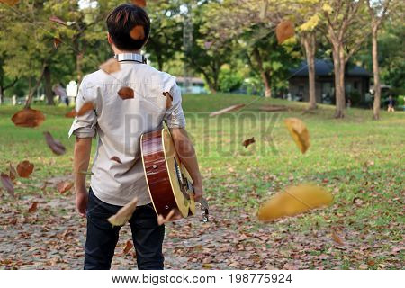 Portrait of young man holding acoustic guitar against among falling leaves in the park