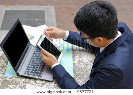 Handsome business man holding his tablet for his work in the park outdoors