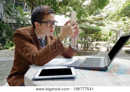 Wide angle shot of handsome business man looking his smartphone for his work in the park outdoors