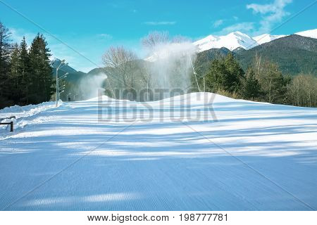 Green pine trees, white snow peaks of the mountains, ski slope and snow canons in Bansko, Bulgaria