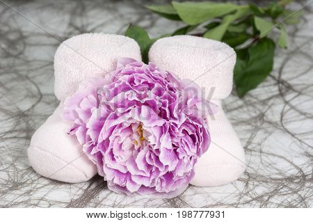 Pair of bootees for newborn girl with one peony with drops of water