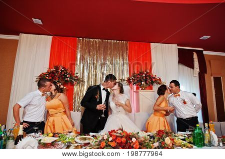 Wedding Couple And Groomsmen With Bridesmaids Kissing By The Table.