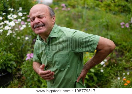 Old man having lumbago pain while walking in the park