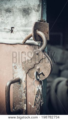 Old open padlock with key on a chain. Photo toned. Art photo. Added grain.