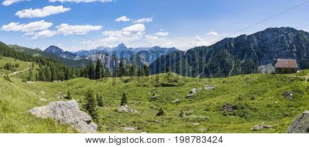 View from Auernig Alm with old huts on Nassfeld in Carnic Alps to Julian Alps in Italy